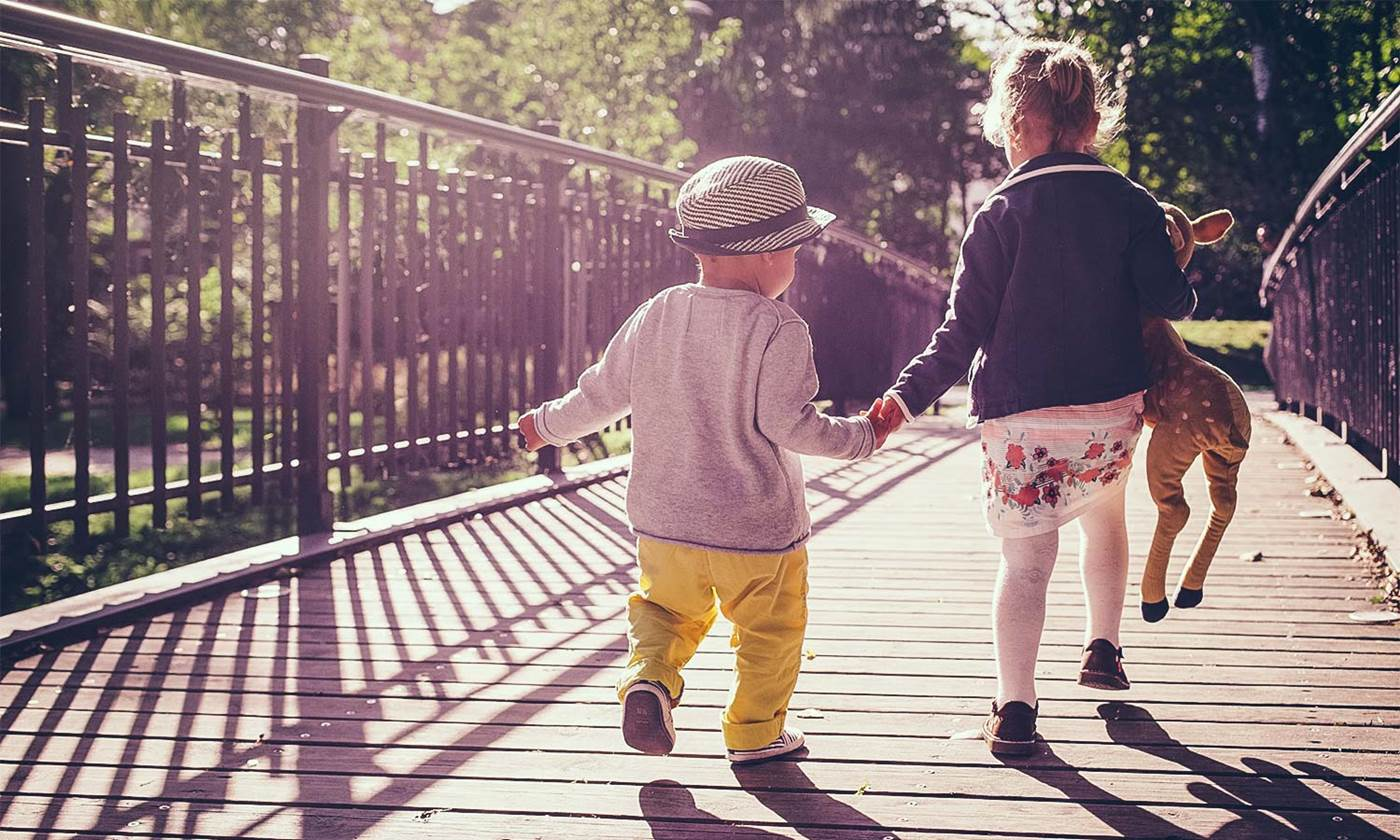 sister and little brother walking on a bridge