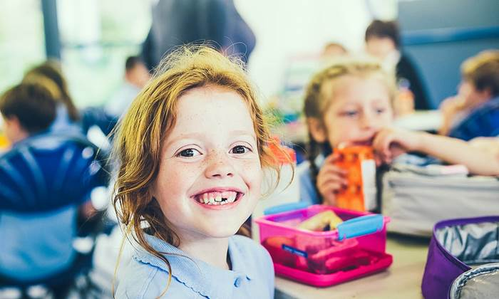 Smiling girl with a missing tooth with a healthy lunch