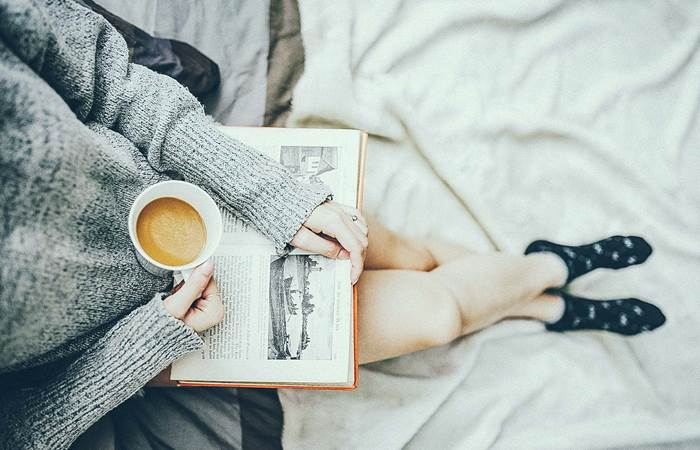 Woman having coffee and reading a book