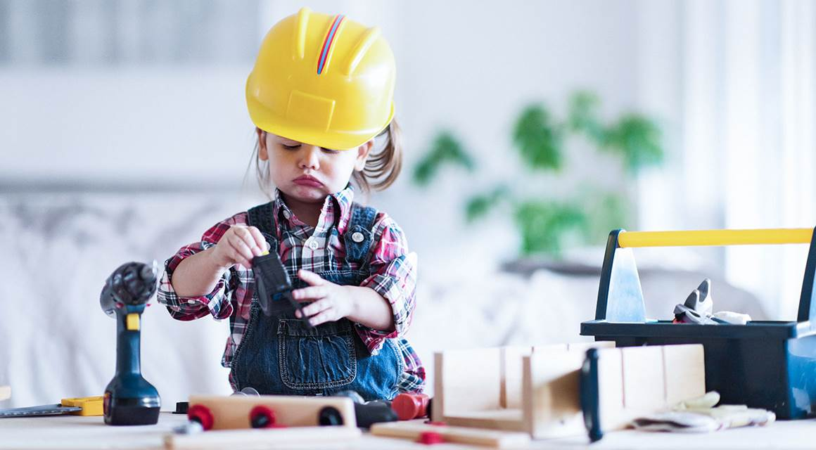 Litte girl playing at being a carpenter