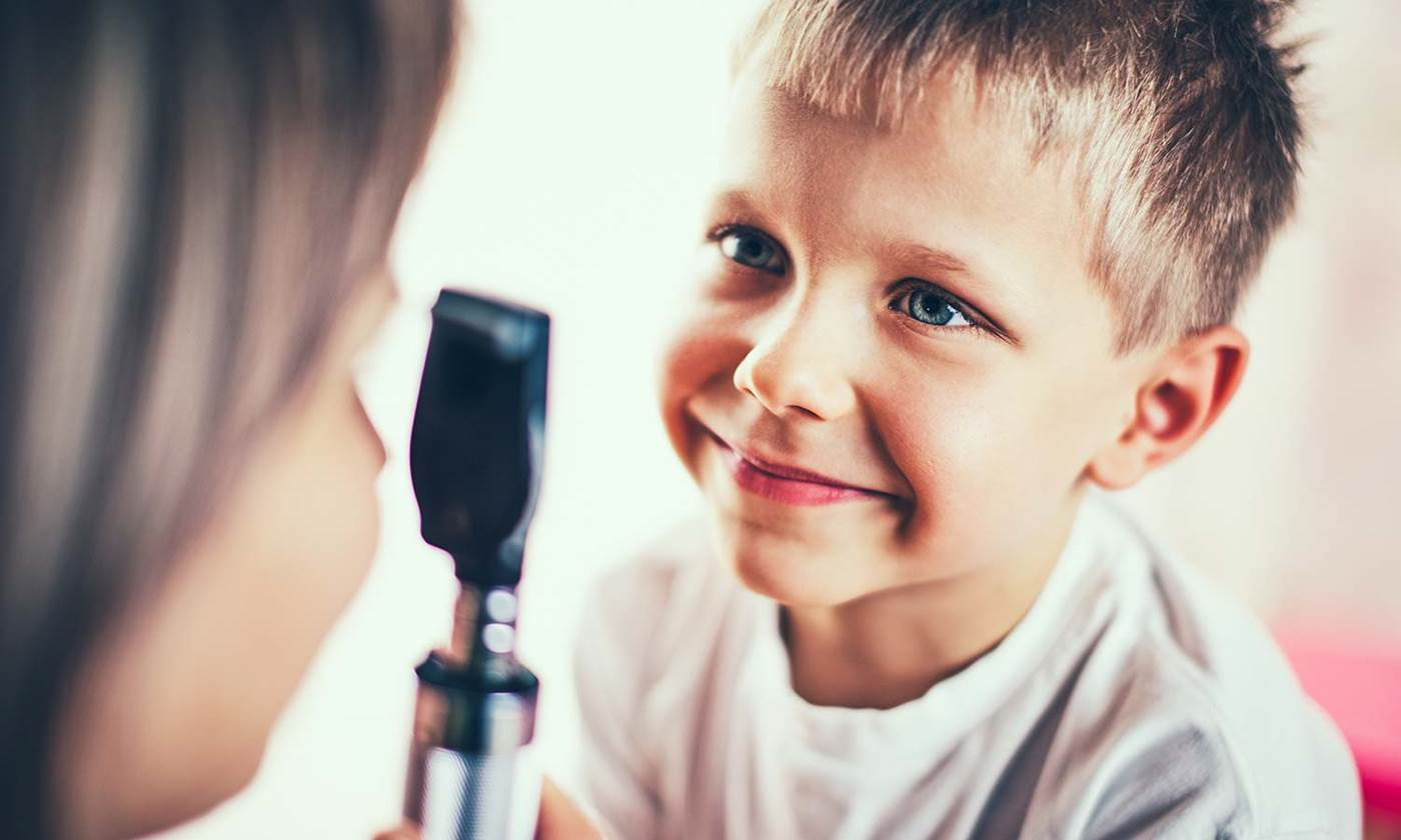 Doctor is examining eyes of the little boy