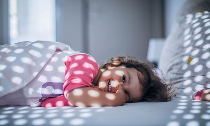 Little girl waking up in bed