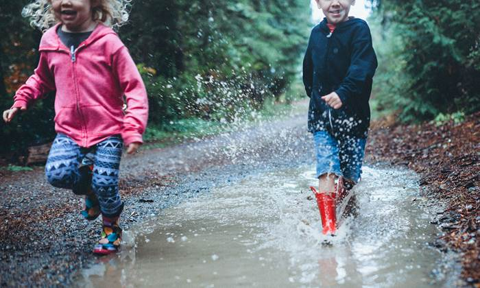 Children wearing rain boots splash and play in a mud puddle