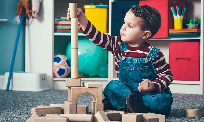 Boy building with wooden blocks