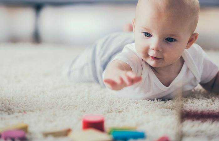Baby on the floor with coloured blocks