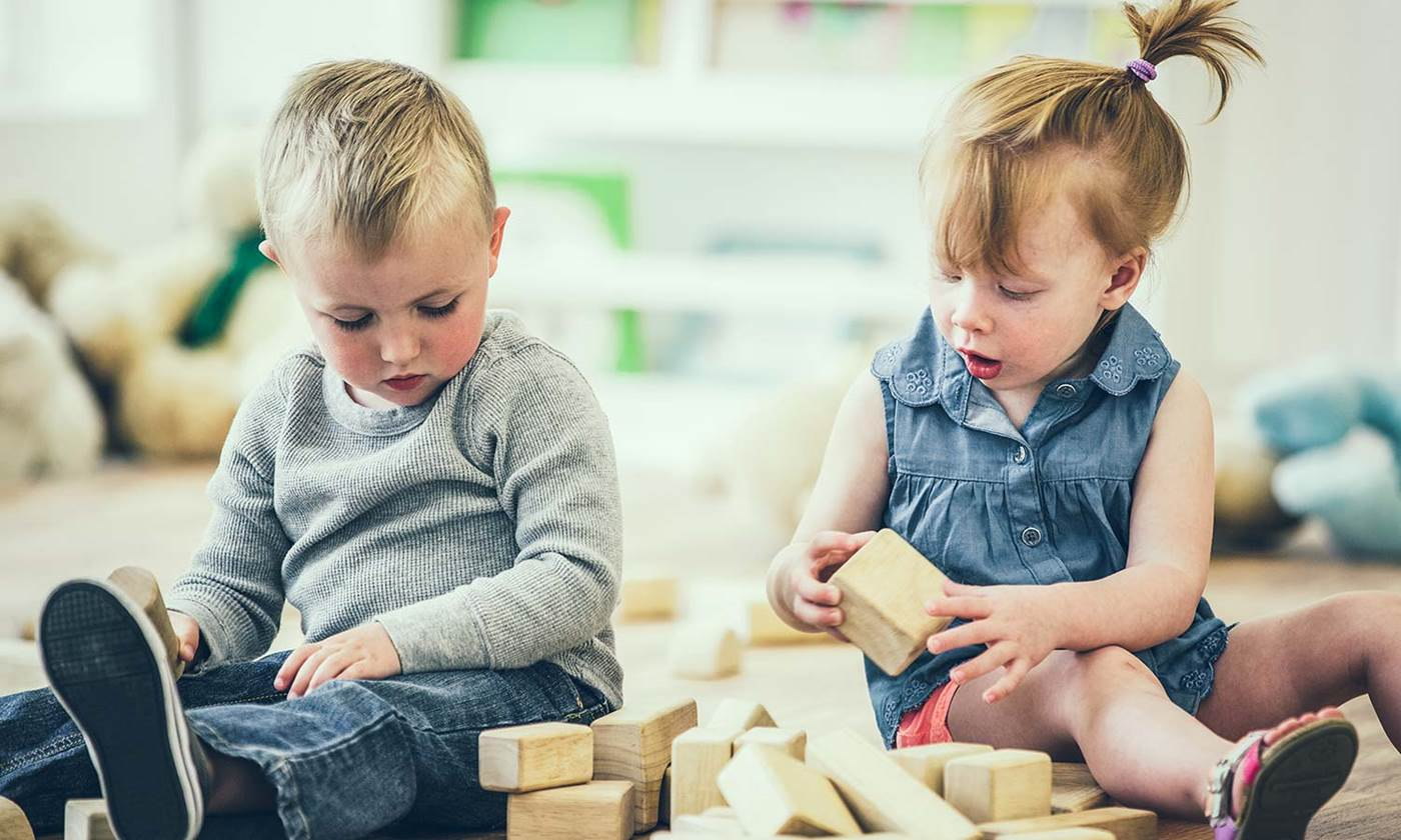 Boy and girl sharing blocks