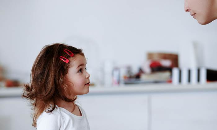 Profile view of girl listening to her mother