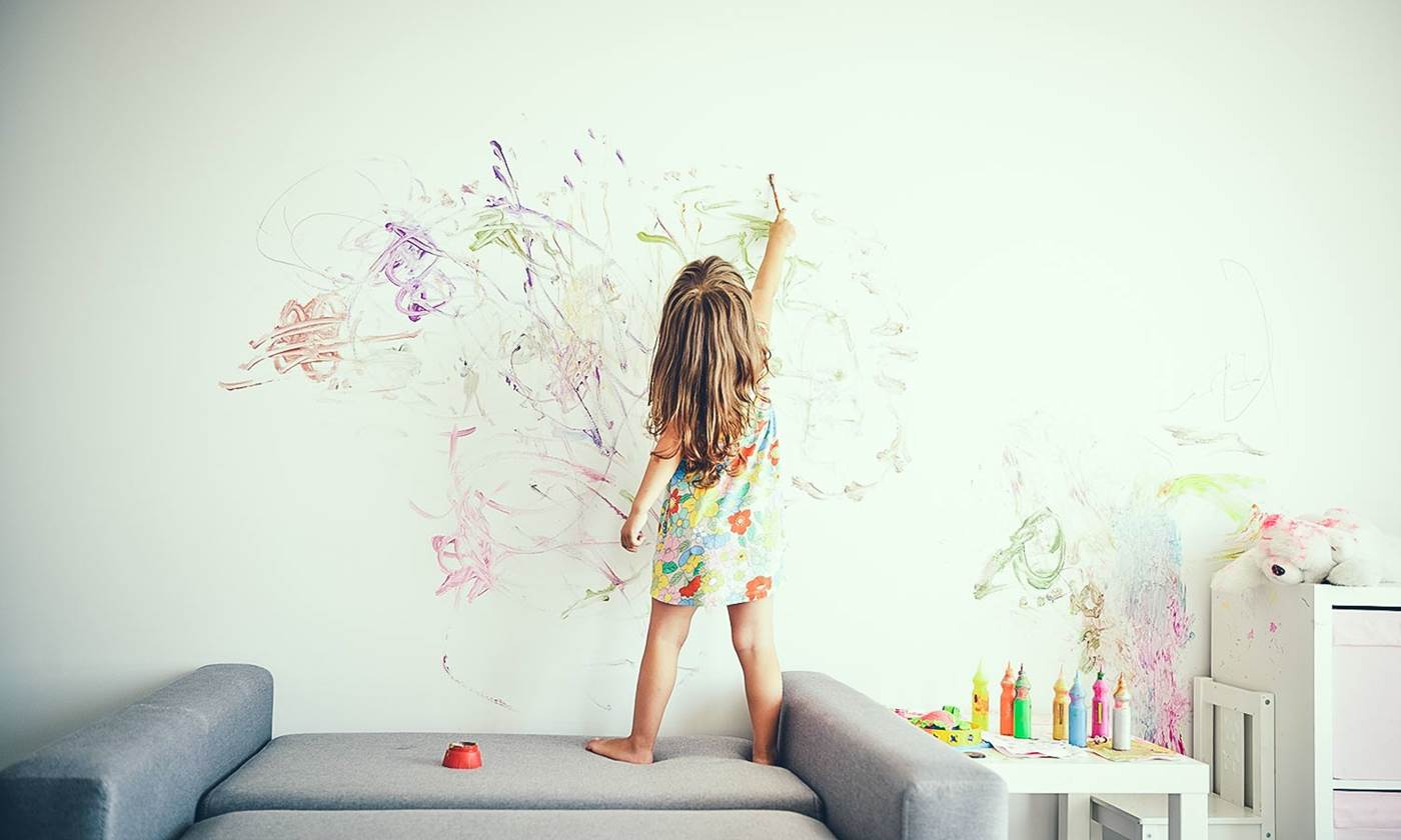 Little girl painting a wall