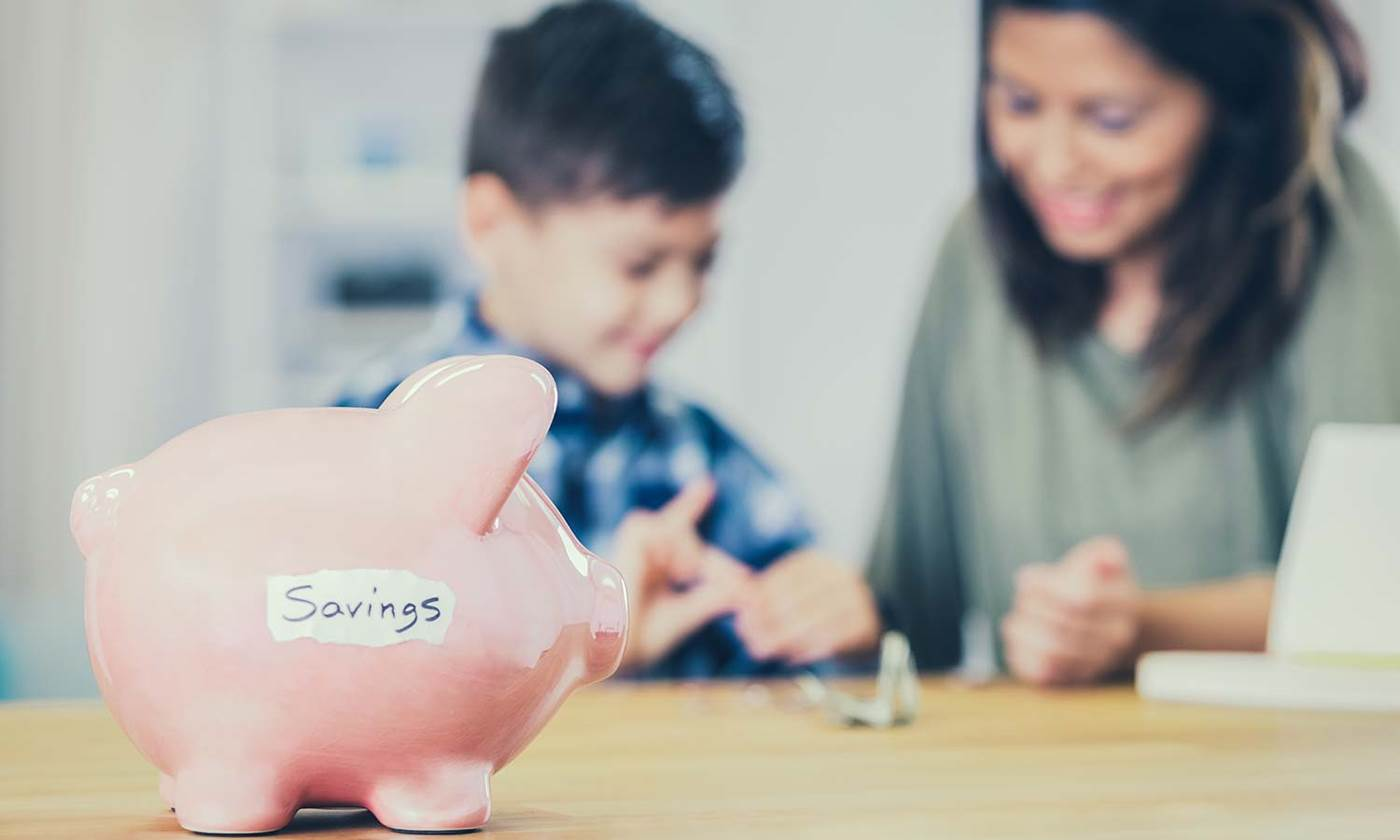 mother and son counting change from piggy bank