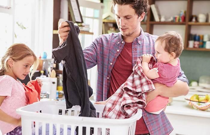 father and child sorting laundry at home