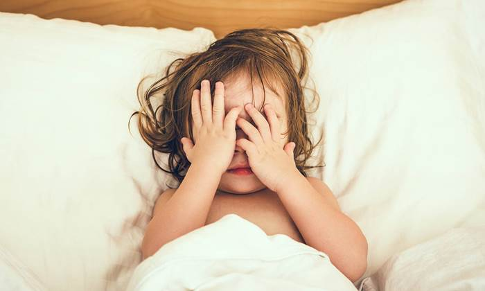 Little girl in bed covering her eyes