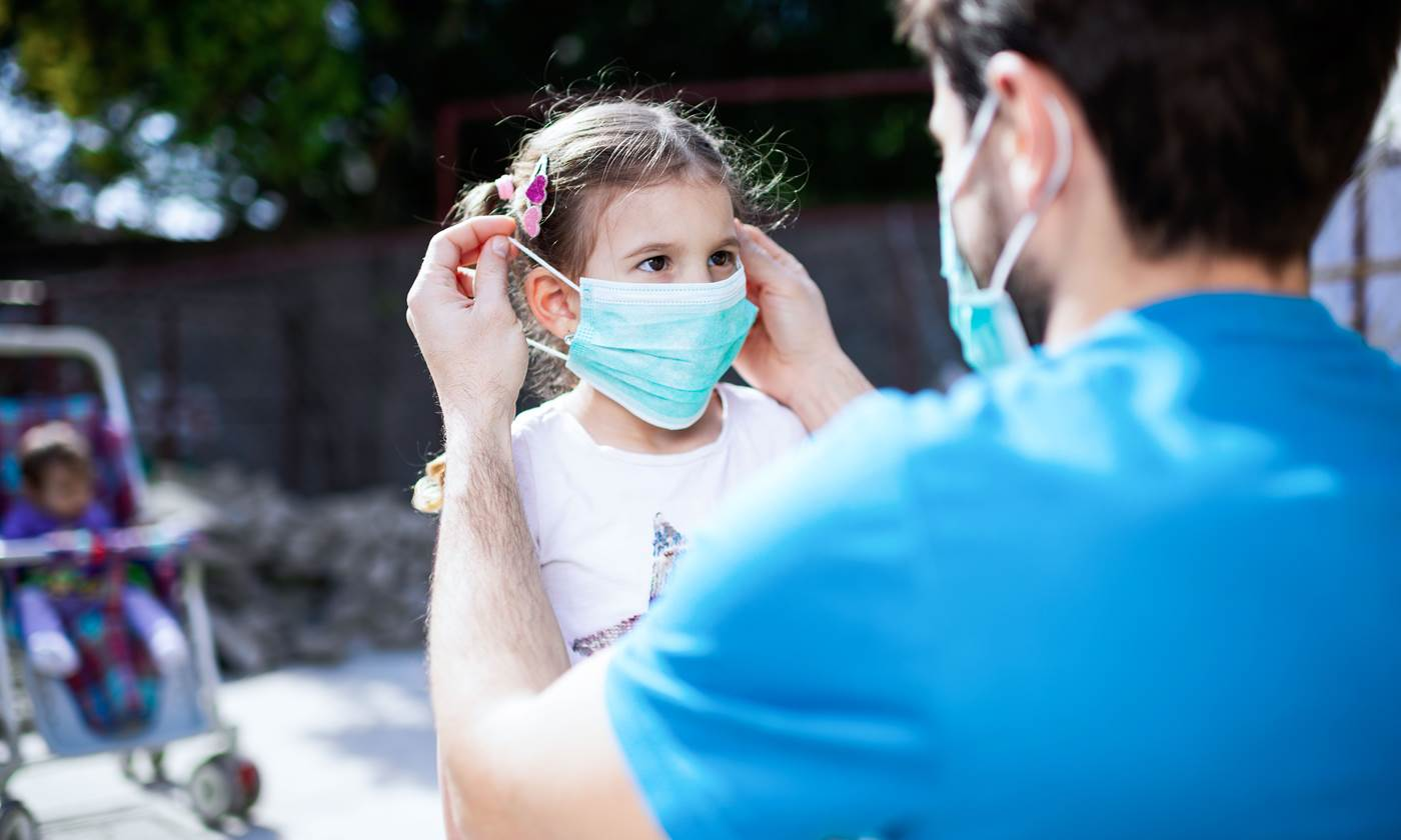 Father applying pollution mask to his daughter.