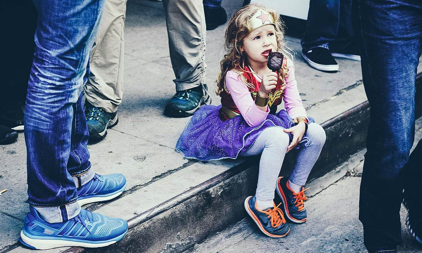 Little girl sitting in the gutter eating ice-cream