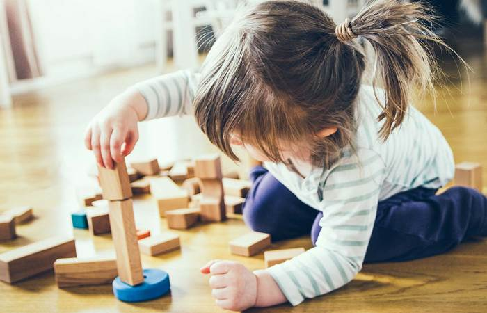 Girl building a tower of wooden blocks