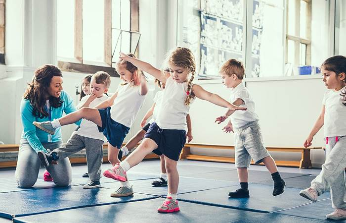 Small children learning to balance encouraged by a teacher