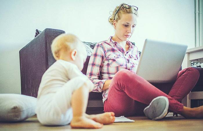 woman working on computer while baby plays