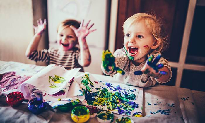 Cheerful children having fun doing finger painting