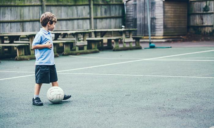 Boy in school uniform playing soccer alone in the school yard