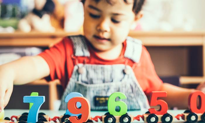 Little boy playing with a mathematics wooden toy