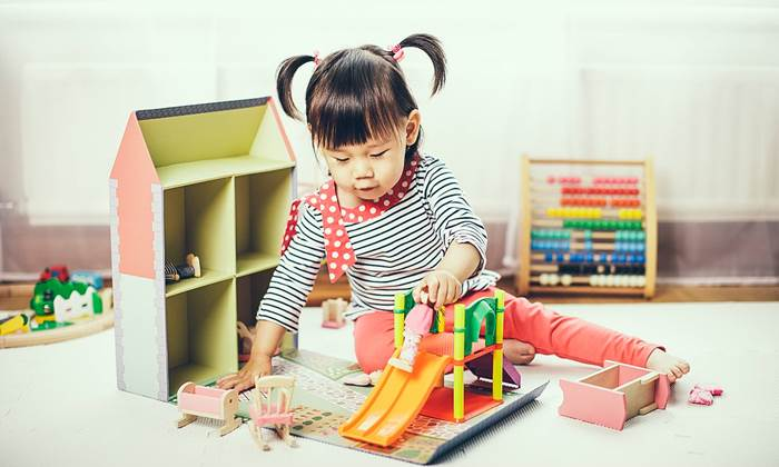 Baby girl playing doll house