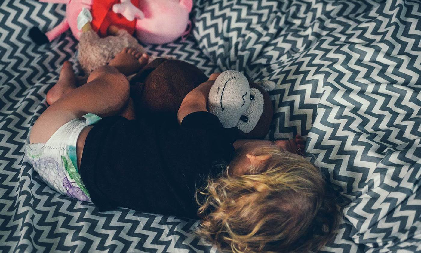 Toddler sleeping with toy monkey