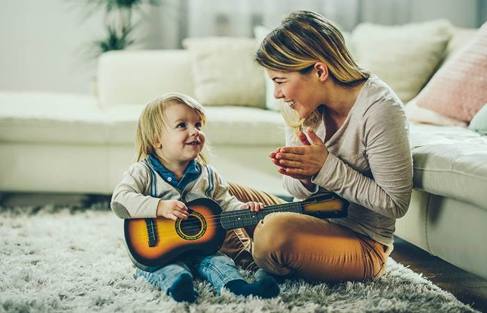 Child being praised for learning the guitar