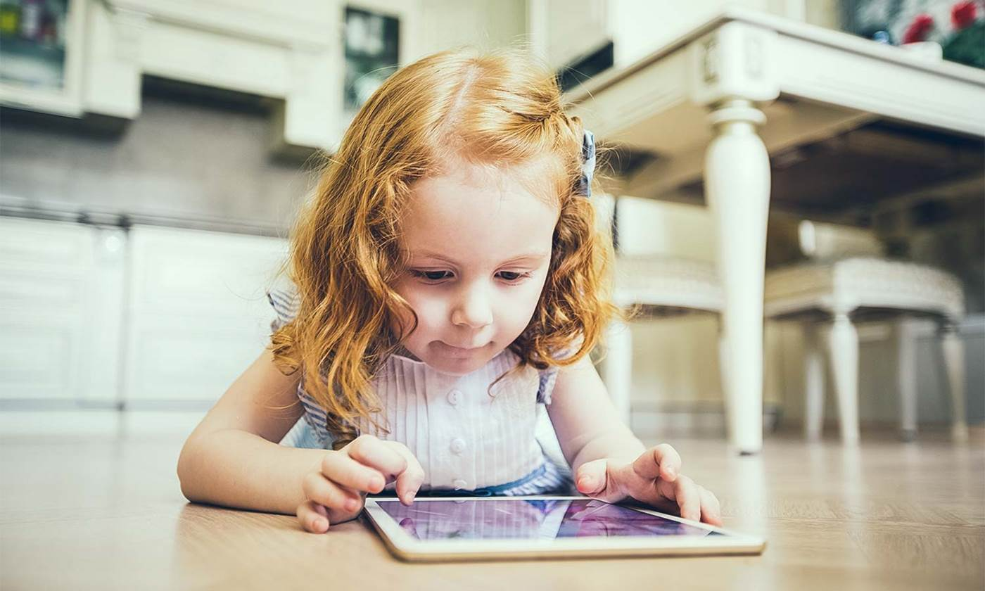 Young girl plays on an iPad