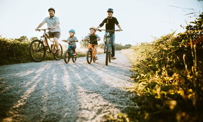 A father and mother ride mountain bikes together with their two small children.