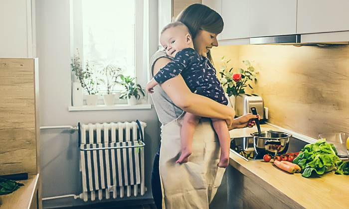 Mum cooking in the kitchen with a baby