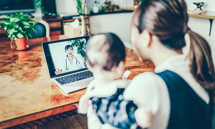 Mother and baby looking at a doctor on a computer