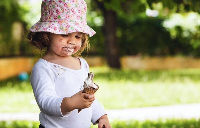 Girl standing in park eating ice cream that is melting.