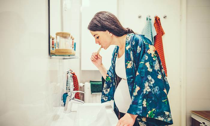 Pregnant woman brushing her teeth