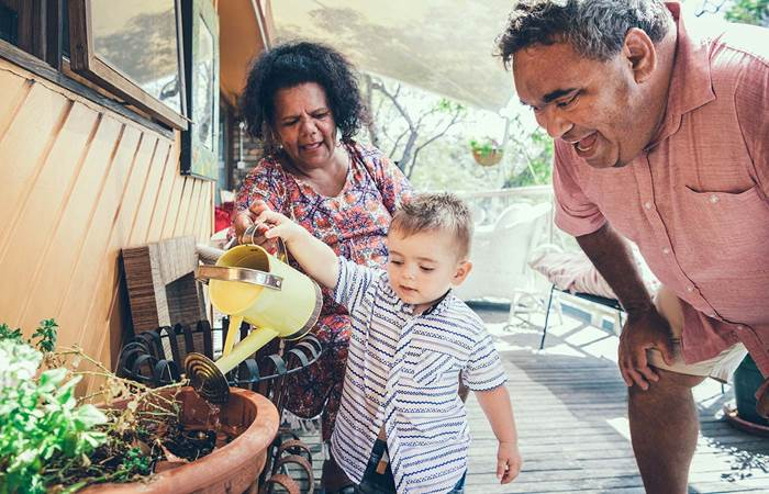 Baby boy watering plants with grandparents